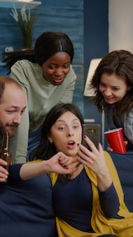 Amici multirazziali che escono a tarda notte guardando video di intrattenimento divertenti su smartphone mentre si rilassano sul divano in soggiorno