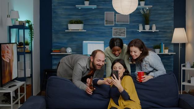 Amici multirazziali che escono insieme a socializzare mentre guardano video divertenti sullo smartphone. gruppo di persone multietniche sedute sul divano a tarda notte in soggiorno a bere birra