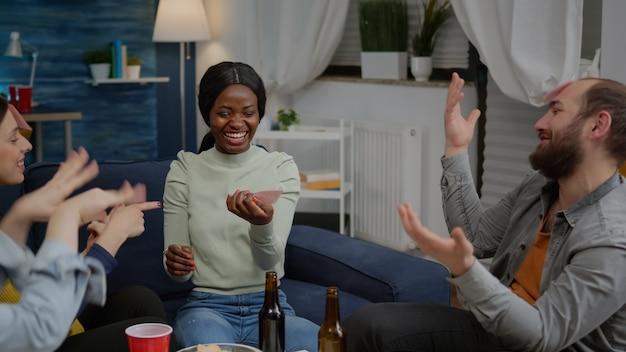 Amici multirazziali che giocano a indovinare chi gioca con fogli appiccicosi attaccati sulla fronte. persone di razza mista che si divertono, ridono insieme mentre sono sedute sul divano in soggiorno a tarda notte