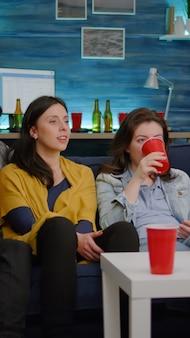 Amici multirazziali seduti sul divano a guardare film divertenti in televisione durante la festa a casa a tarda notte in soggiorno. gruppo di persone di razza mista che bevono birra, mangiano spuntini e si godono il tempo insieme