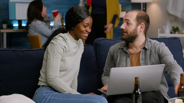 Amici multirazziali che socializzano mentre guardano video online sul laptop rilassandosi sul divano. sullo sfondo due donne che bevono birra si godono il tempo trascorso insieme durante la festa di intrattenimento