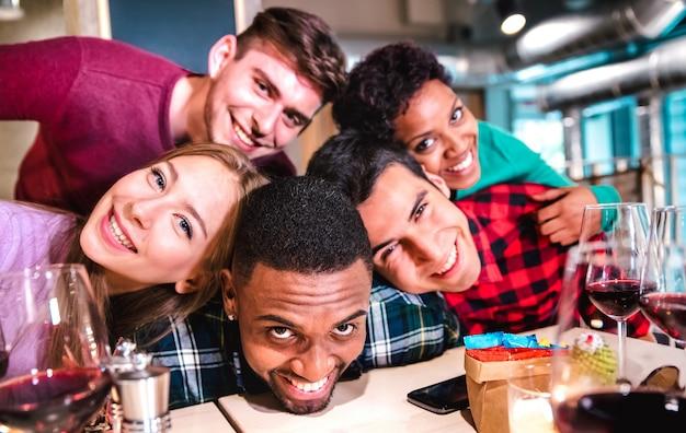 Amici multirazziali che prendono selfie ubriachi al ristorante della cantina di fantasia