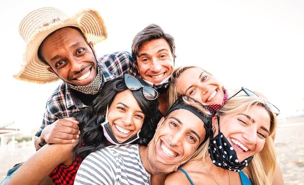 Amici multirazziali che prendono selfie sorridenti sopra maschere facciali aperte