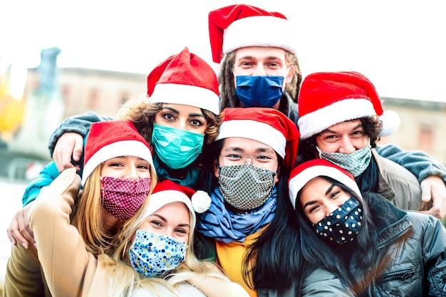 Amici multirazziali che prendono selfie indossando maschera per il viso e cappello da babbo natale - focus sul ragazzo dell'asia centrale