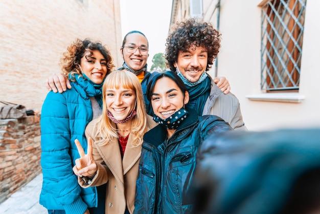 Amici multirazziali che indossano maschera facciale prendendo selfie indossando abiti invernali
