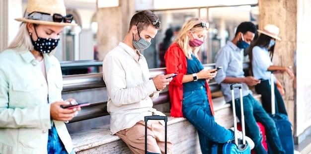 Amici multirazziali che indossano una maschera facciale utilizzando telefoni cellulari intelligenti - concentrati sul primo ragazzo a sinistra