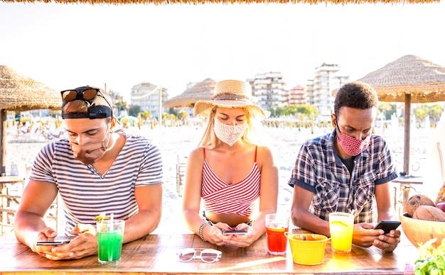 Amici multirazziali con maschere chiuse che utilizzano l'app di monitoraggio con smartphone mobili