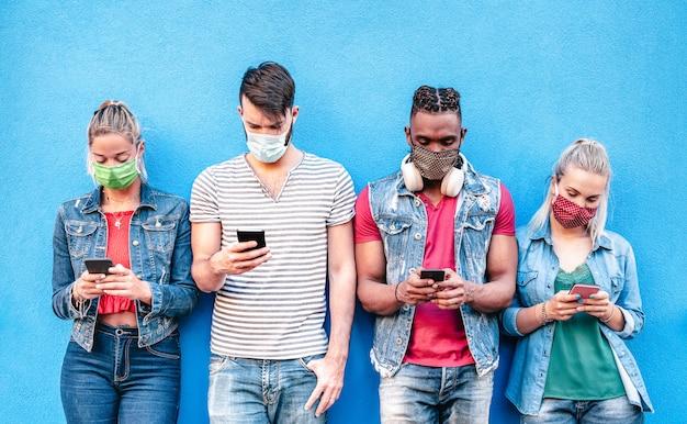 Amici multirazziali con maschere per il viso che utilizzano l'app di monitoraggio con smartphone mobili