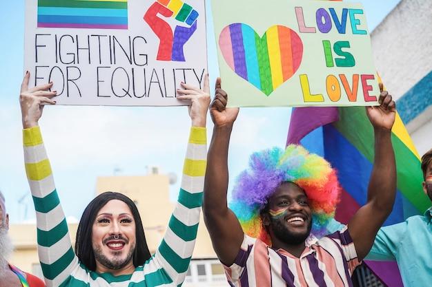 Gay multirazziali che marciano alla parata dell'orgoglio lgbt con striscioni - focus sulla drag queen
