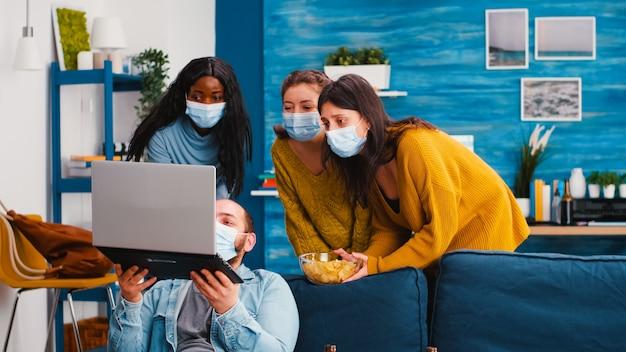 Gruppo multirazziale di amici che navigano utilizzando il laptop mantenendo le distanze sociali e indossando una maschera facciale per prevenire la diffusione del covid e l'infezione nel soggiorno dell'appartamento