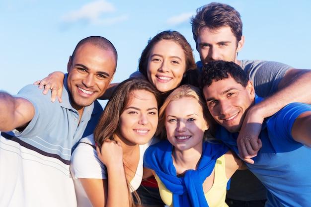 Gruppo multirazziale di amici che si fanno selfie in spiaggia