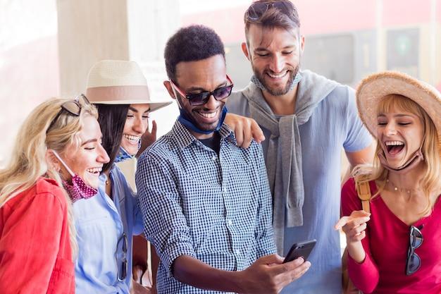 Gruppo multirazziale di amici che indossano la maschera per il viso utilizza lo smartphone alla stazione ferroviaria