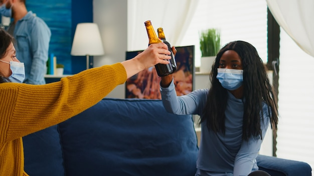 Gruppo multirazziale di amici con maschere che si godono una birra durante la nuova festa normale in soggiorno rispettando la distanza sociale per prevenire la diffusione del virus. diverse persone che si godono il tempo libero nella pandemia globale