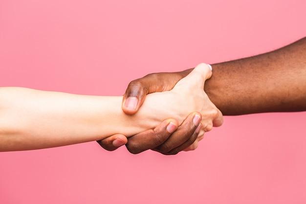 Stretta di mano multirazziale tra l'uomo africano nero e la donna caucasica bianca