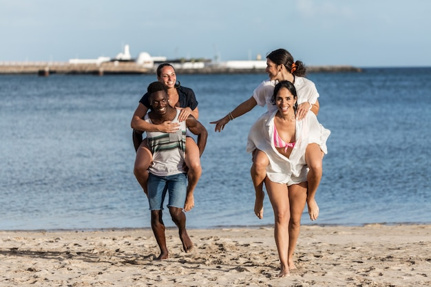 Uomo e donna multirazziali che fanno un giro sulle spalle alle amiche sulla spiaggia