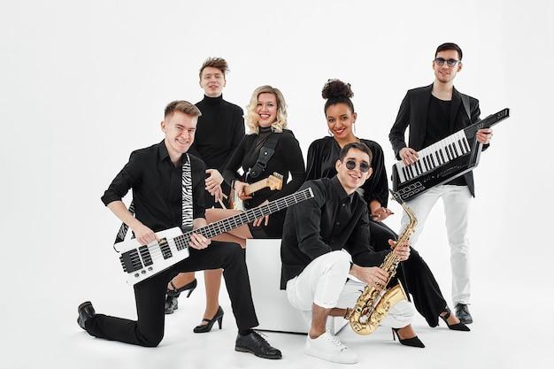 Banda musicale multirazziale su uno spazio bianco. un gruppo di musicisti internazionali che provano una performance di concerto. cantante, montone, chitarrista