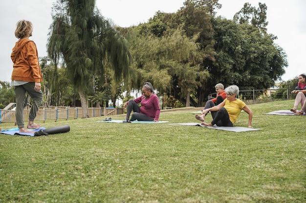 Persone multirazziali che fanno lezione di yoga all'aperto nel parco cittadino