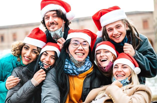 Persone multirazziali che prendono selfie di natale che indossano maschera e cappello da babbo natale