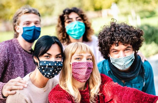 Persone multirazziali che prendono selfie indossando maschera per il viso e abiti primaverili