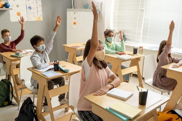 Scolari multirazziali in maschera alzando la mano per rispondere alla domanda dell'insegnante