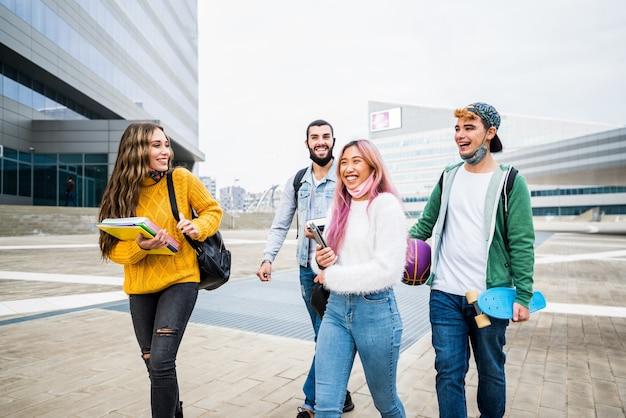 Studenti multirazziali che camminano sulla strada della città