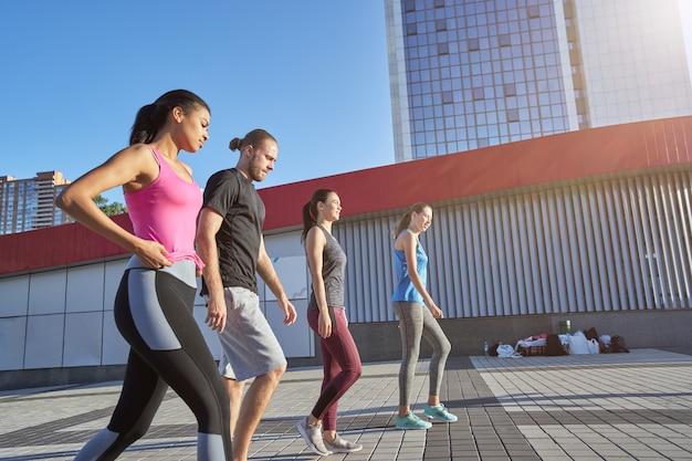 Squadra multirazziale di sportivi che camminano lungo l'area soleggiata