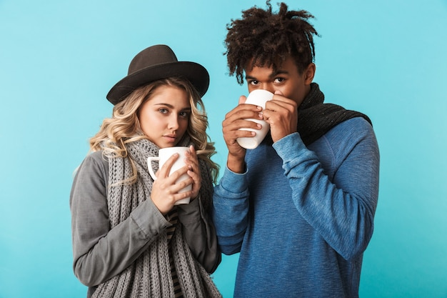 Multirazziale coppia di adolescenti che indossa abiti invernali in piedi isolato sul muro blu, tenendo tazze di tè
