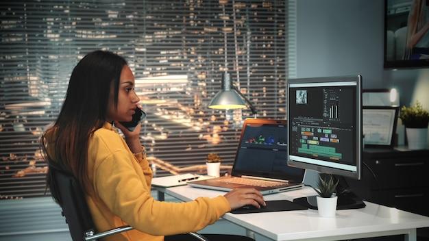 Editor video e audio multirazziale che parla con qualcuno tramite smartphone e montaggio di video