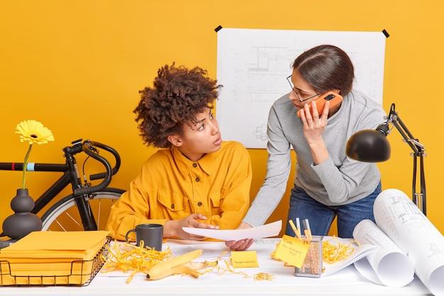 Le donne architetto multirazziali discutono del futuro progetto di ingegneria, le scartoffie posano al deskstop creano progetti?