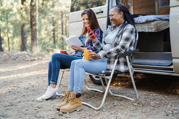 Amiche multirazziali che si divertono in campeggio con il camper mentre leggono libri e bevono caffè all'aperto - concetto di viaggio e natura - focus principale sul volto femminile africano