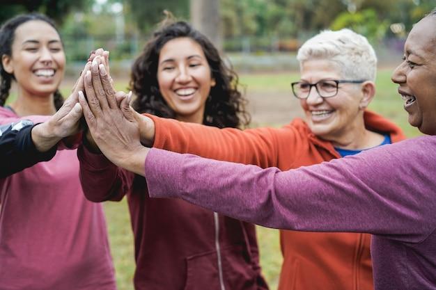 Donne multirazziali che impilano le mani all'aperto al parco cittadino - obiettivo principale sulla mano della donna africana