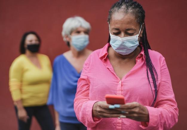 Donne multirazziali in attesa in fila mentre indossano maschere di sicurezza per il coronvirus - donna africana anziana che utilizza smartphone