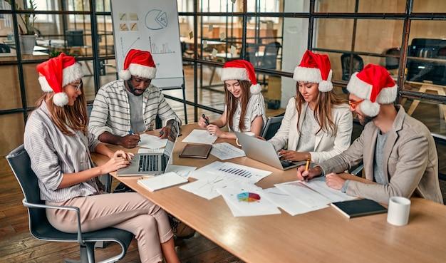 I giovani creativi multirazziali stanno celebrando le vacanze in un ufficio moderno. un gruppo di giovani imprenditori è seduto in cappelli di babbo natale nell'ultimo giorno lavorativo.