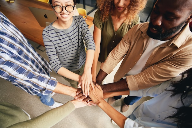Giovani multirazziali che uniscono le mani per lo spirito di squadra
