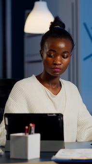 Multitasking donna d'affari nera che lavora al laptop e tablet allo stesso tempo facendo gli straordinari in ufficio di avvio. impiegato africano impegnato che analizza le statistiche finanziarie che sovraccaricano la scrittura, la ricerca.