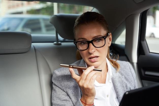 Ritratto multitasking di una donna d'affari impegnata e sicura che utilizza tablet e smartphone digitali