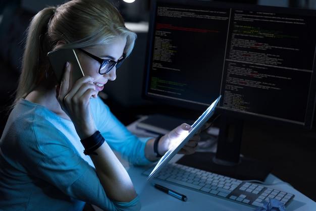 Responsabilità multitasking. sorridente receptionist esperto piacevole seduto in ufficio e utilizzando gadget moderni mentre esprime concentrazione e parla al telefono