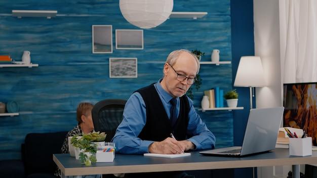 Uomo in pensione multitasking che legge sul laptop e scrive sul notebook che lavora da casa focalizzato sul vecchio rem...