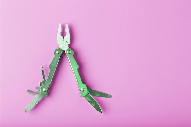 Multitool è uno strumento multifunzionale su uno sfondo rosa. il concetto di un multiutensile aperto e volante con spazio libero.