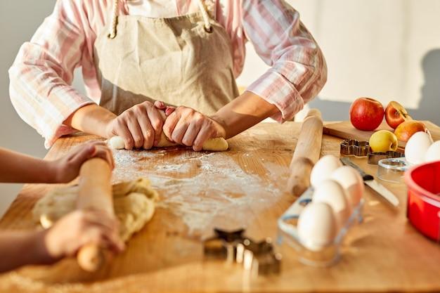 La mamma insegna alla figlia a fare il lavoro di pasta usa il perno del rullo in cucina, madre caucasica che cucina panini da forno o torta con piccola ragazza bambino in età prescolare
