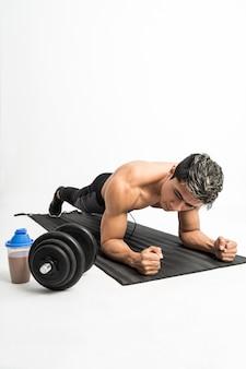 L'uomo muscoloso senza vestiti fa esercizi di plancia con un tappetino accanto alla bottiglia e al manubrio