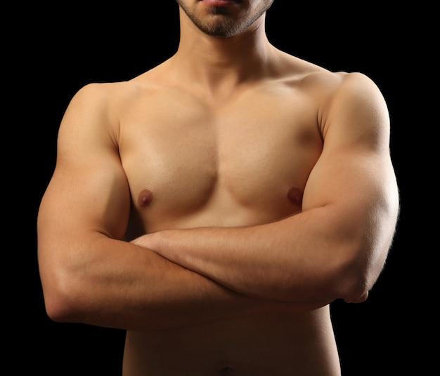 Giovane muscolare su oscurità