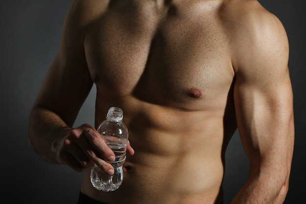 Giovane muscolare che tiene una bottiglia d'acqua sul nero