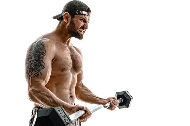 Uomo di bodybuilder atleta muscolare in pantaloni mimetici con un allenamento a torso nudo con manubri su un muro bianco. isolato