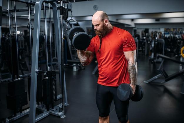 Atleta muscolare facendo esercizio con manubri in palestra. uomo barbuto in club sportivo, stile di vita sano