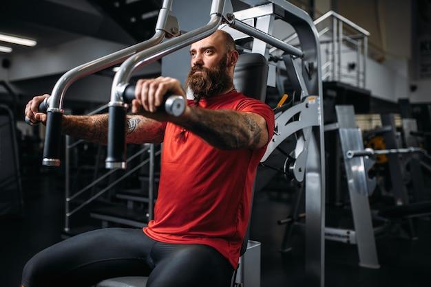 Atleta muscolare sulla macchina ginnica in palestra. uomo barbuto in allenamento nel club sportivo, uno stile di vita sano