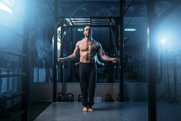 Atleta muscolare esercizi con corda per saltare in palestra. sportivo su allenamento fitness.