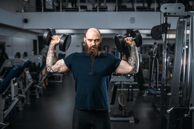 Atleta muscolare posa con manubri, allenamento in palestra. sportivo barbuto in allenamento nel club sportivo, stile di vita sano