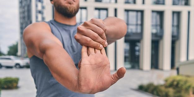 Atleta muscoloso con la barba allunga le braccia prima dell'allenamento stando in piedi per strada