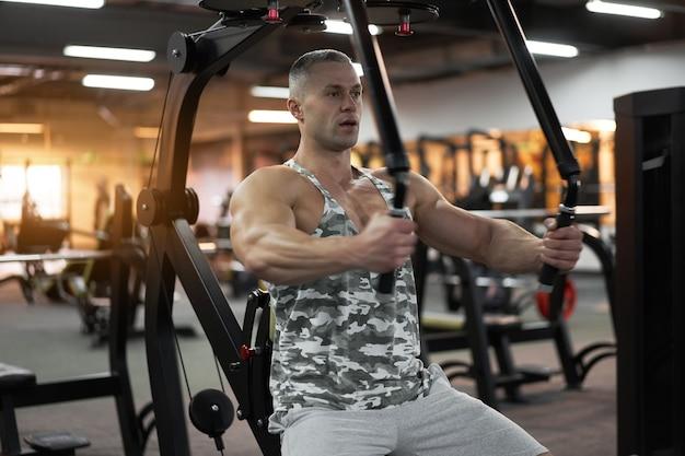 Culturista atletico muscolare che si siede sui muscoli del torace allenamento panca su attrezzature per il fitness